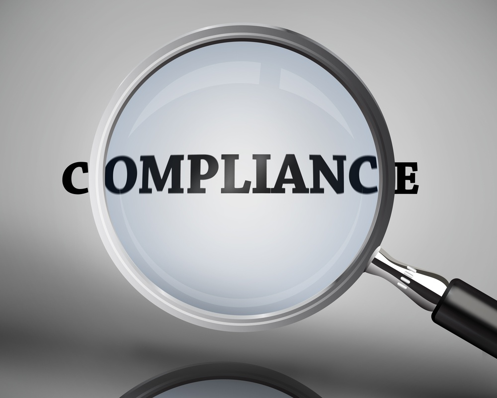 Magnifying glass showing compliance word on grey background